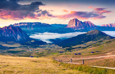 Colorful summer sunrise in Dolomite Alps. August in Gardena valley. View of Sassolungo (Langkofel) mountain range, Ortisei, S. Cristina location, Province of Bolzano, South Tyrol, Italy.