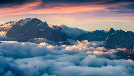 bolzano province: Foggy morning scene in the Val di Fassa valley. View from the birds eye from Sella pass, Province of Bolzano - South Tyrol. Sunrise in Dolomite Alps, Italy, Europe. Dramatic summer landscape.