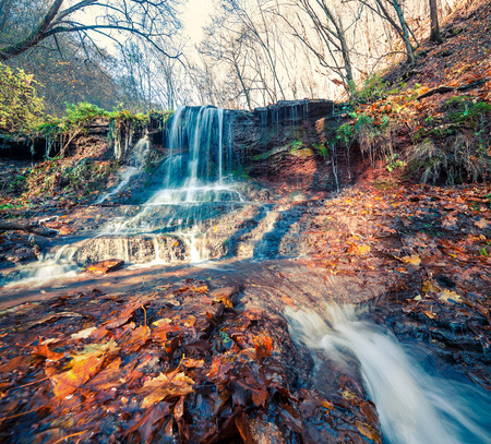 Sunny autumn view in the forest with pure water waterfall. Beautiful outdoor scene near Rusyliv village, Ukraine, Europe. Artistic style post processed photo.