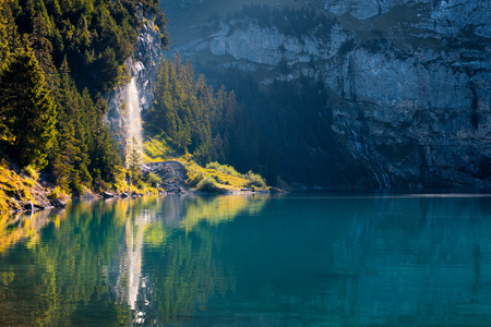the bernese oberland: Pure water watterfall on unique lake - Oeschinen (Oeschinensee). Beautiful outdoor scene in Bernese Oberland Alps, Switzerland, Europe. Stock Photo