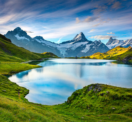 Wetterhorn and Wellhorn peaks over Bachsee lake. Colorful summer scene in Bernese Oberland Alps, Grindelwald location, Innertkirchen, Switzerland, Europe. Stock Photo