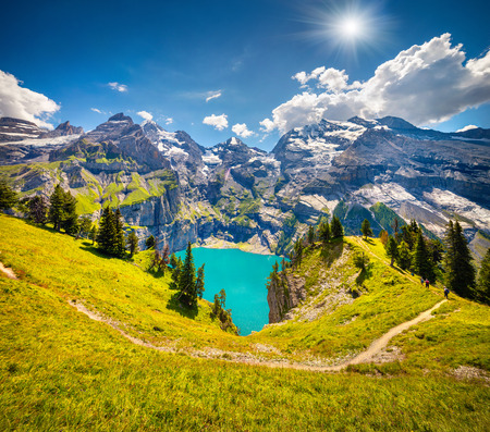 Colorful summer morning on unique lake - Oeschinen (Oeschinensee). Beautiful outdoor scene in Bernese Oberland Alps, Switzerland, Europe.