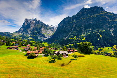 Colorful morning view of Grindelwald village valley from cableway. Wetterhorn and Wellhorn mountains, located west of Innertkirchen in the Bernese Oberland Alps. Switzerland, Europe.