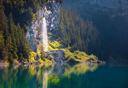 Pure water watterfall on unique lake - Oeschinen (Oeschinensee). Beautiful outdoor scene in Bernese Oberland Alps, Switzerland, Europe. Banco de Imagens