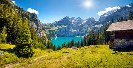 Colorful summer morning on unique lake - Oeschinen (Oeschinensee), UNESCO World Heritage Site. Beautiful outdoor scene in Bernese Oberland Alps, Switzerland, Europe.