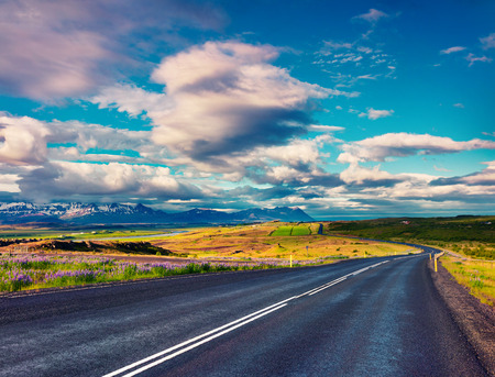 Empty asphalt road with colorful cloudy sky. Beautiful outdoor scenery in Iceland, Europe. Image of travel concept background Stock Photo