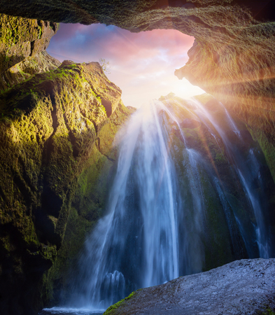 Bottom view of beautiful waterfall - Seljalandfoss. Colorful summer sunrise in canyon in Iceland, south region, Europe. Artistic style post processed photo. Standard-Bild