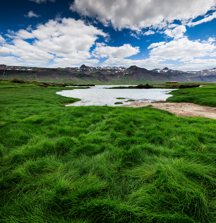 Green grass valley in the volcanic mountains foothill. Sunny summer landscape in the west coast of Iceland, Europe. Artistic style post processed photo.