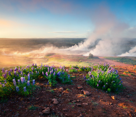 Erupting of the Great Geysir lies in Haukadalur valley on the slopes of Laugarfjall hill. Foggu summer morning in Southwestern Iceland, Europe. Artistic style post processed photo. Stock Photo