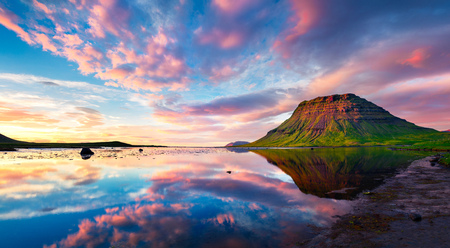 Colorful summer sunset with Kirkjufell Mountain in Grundarfjordur town. Evening scene on the Snaefellsnes peninsula, Iceland, Europe. Artistic style post processed photo.