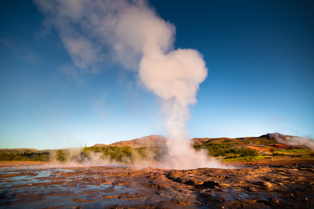 Erupting of the Great Geysir lies in Haukadalur valley on the slopes of Laugarfjall hill. Erlie morning in Southwestern Iceland, Europe. Artistic style post processed photo.