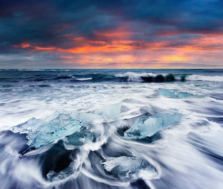 obrero: Blocks of ice washed by the waves on Jokulsarlon beach. Dramatic summer sunrise in Vatnajokull National Park, southeast Iceland, Europe.Artistic style post processed photo. Foto de archivo
