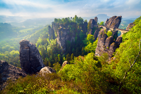 Misty morning on sandstone cliff in Saxony Switzerland with Bastei bridge. Colorful spring scene in Germany, Saxony, Europe. Artistic style post processed photo. Stock Photo