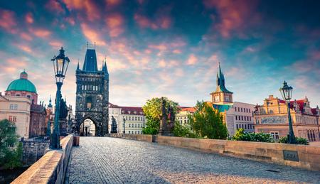 Sonnige Frühlingsszene auf der Karlsbrücke an der Moldau (Karluv Most) mit Statuen und der Kirche des Heiligen Franziskus von Assisi. Bunter Sonnenaufgang in Prag, Tschechische Republik, Europa. Standard-Bild - 77962555