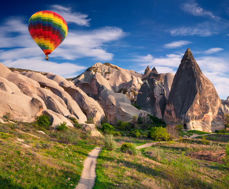Flying on the balloons early morning in Cappadocia. Colorful sunrise in Red Rose valley, Goreme village location, Turkey, Asia. Artistic style post processed photo. Stock Photo