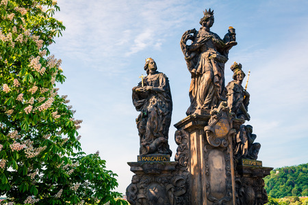 Sculpture of St.Margarita and St. Elisabeth on the Charles Bridge in Prague. Colorful spring morning in capital of Czech Republic, Europe.