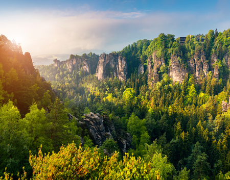 Misty morning on sandstone cliff in Saxon Switzerland National Park. Colorful spring sunrise in Germany, Saxony, Europe. Artistic style post processed photo. Stock Photo