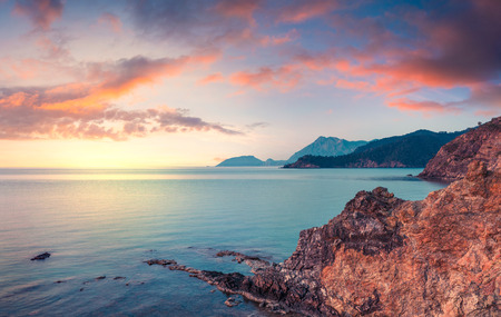 Few minutes before the sunrise on the Mediterranean sea in April. Colorful morning scene in the small bay near Tekirova village, District of Kemer, Antalya Province. Artistic style post processed photo. Stok Fotoğraf - 77972632