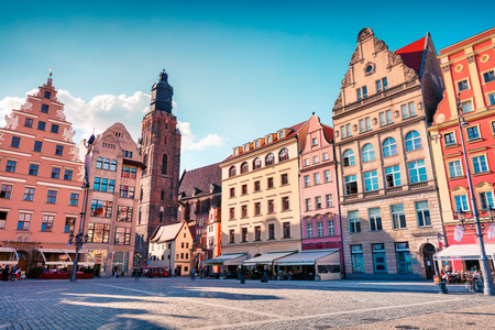 Colorful morning scene on Wroclaw Market Square. Sunny cityscape in historical capital of Silesia with beautiful old houses and St. Ekisabeth church, Poland, Europe. Artistic style post processed photo.