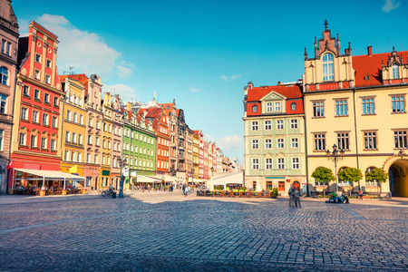 Colorful morning scene on Wroclaw Market Square. Sunny cityscape in historical capital of Silesia with beautiful old houses, Poland, Europe. Artistic style post processed photo.