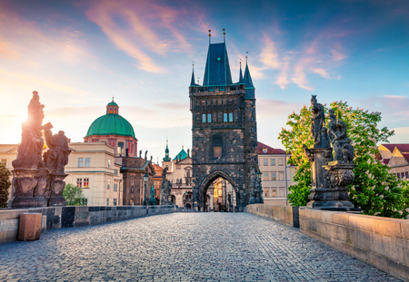 Sunny spring scene on Charles bridge on Vltava river (Karluv Most) with statues and Saint Francis of Assisi Church. Colorful sunrise in Prague, Czech Republic, Europe.