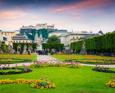 ミラベル庭園から古い歴史的な要塞ホーエン ザルツブルク城とザルツブルク大聖堂の夕景。オーストリア、ヨーロッパのカラフルな夕日。芸術的な