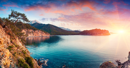 Picturesque Mediterranean seascape in Turkey. Dramatic sunrise in a small bay near the Tekirova village, District of Kemer, Antalya Province. Artistic style post processed photo. Stok Fotoğraf - 77991207