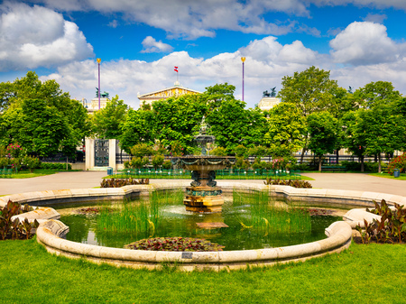 borne fontaine: Picturesque scene in Volksgarten with fountain and Austrian parliament building. Sunny spring  view in Vienna, Austria, Europe. Artistic style post processed photo.
