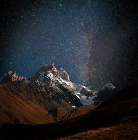 Night view of Ushba mountain with dark starry sky. Beautiful outdoor scene in the Caucasus mountains, Upper Svaneti, Europe.