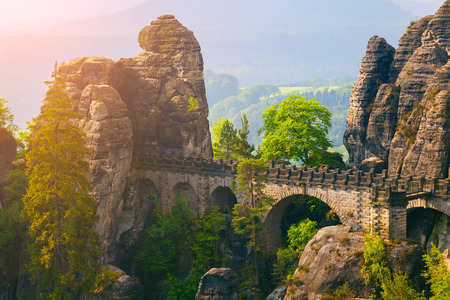 Misty morning on sandstone cliff in Saxon Switzerland National Park with Bastei bridge. Colorful spring sunrise in Germany, Saxony, Europe. Artistic style post processed photo. Stock Photo