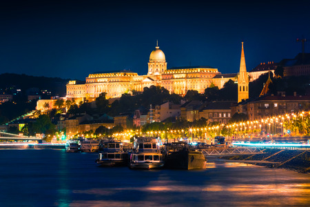 Evening view of Buda Castle with city lights and ship on the Danube river. Colorful cityscape in Budapest, Hungary, Europe. Artistic style post processed photo.