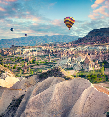 Flying on the balloons early morning in Cappadocia. Colorful spring scene in Red Rose valley, Goreme village location, Turkey, Asia. Artistic style post processed photo.