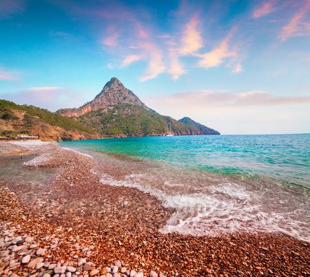 Picturesque Mediterranean seascape in Turkey. Colorful spring sunrise on Adrasan beach with view of Moses Mountain.District of Kemer, Antalya Province. Artistic style post processed photo.
