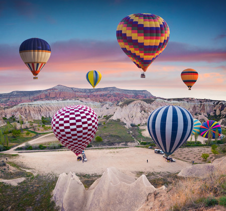 Flying on the balloons early morning in Cappadocia. Colorful sunrise in Red Rose valley, Goreme village location, Turkey, Asia. Artistic style post processed photo. Stok Fotoğraf