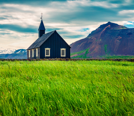 Black wooden Budakirkja church at Saefellsnes. Dramatic summer morning with field of fresh green grass on Snafellsnes peninsula, western Iceland, Europe. Artistic style post processed photo.