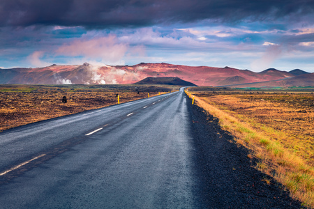 Empty asphalt road with colorful cloudy sky. Beautiful outdoor scenery in the Hverarond geothermal valley, Iceland, Europe. Image of travel concept background
