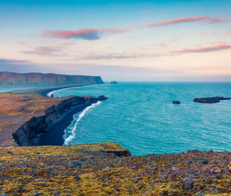 Colorful summer sunset on the Kirkjufjara beach. Evening view of Reynisdrangar cliffs from Dyrholaey peninsula in Atlantic ocean. South Iceland, Vic village location, Europe. Stock Photo