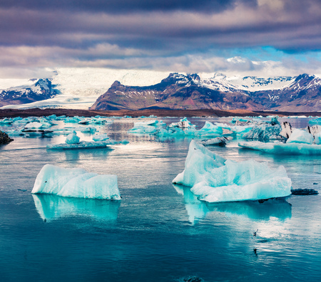 Floating of blue icebergs in Jokulsarlon glacial lagoon. Colorful sunset in Vatnajokull National Park, southeast Iceland, Europe. Artistic style post processed photo. Stock Photo