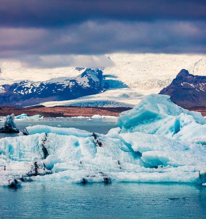 Flottement d'icebergs bleus dans la lagune glaciaire de Jokulsarlon. Coucher de soleil coloré dans le parc national de Vatnajokull, au sud-est de l'Islande, en Europe. Photo artistique après traitement de photo. Banque d'images - 85334259