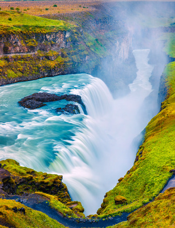 Huge waterfall Gullfoss in the morning mist. Colorful summer scene on Hvita river in southwest Iceland, Europe. Artistic style post processed photo.