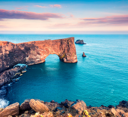 Great evening scene of Dyrholaey arch. Colorful summer sunset in Dyrholaey Nature Reserve, south coast of Iceland, Europe. Artistic style post processed photo.