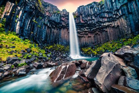 Espectacular vista de la mañana de la famosa cascada Svartifoss (Black Fall). Salida del sol colorida del verano en Skaftafell, parque nacional de Vatnajokull, Islandia, Europa. Foto procesada de estilo artístico. Foto de archivo - 85334008