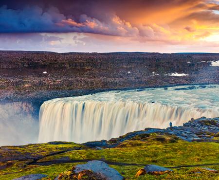 Toeristische bewonderen uitzicht op vallende water van de meest krachtige waterval in Europa - Dettifoss. Kleurrijke zomer zonsopgang in Jokulsargljufur Nationaal Park, IJsland. Artistieke stijl na bewerkte foto. Stockfoto