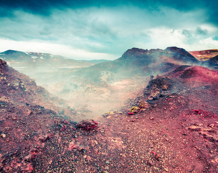 Fields of steamy waters in the Krafla volcano. Colorful exotic landscape with lava ground in the geothermal valley Leirhnjukur, located near Lake Myvatn in north of Iceland, Europe.