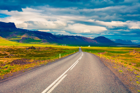 Empty asphalt road with colorful cloudy sky. Beautiful outdoor scenery in Iceland, Europe. Image of travel concept background Banco de Imagens