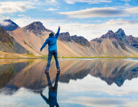 Walking upon the waters surface on the Stokksnes headland on the southeastern Icelandic coast. Man standing on the middle of lake with raised hand and enjoying moment, Vestrahorn (Batman Mountain). Iceland, Europe. Stock Photo