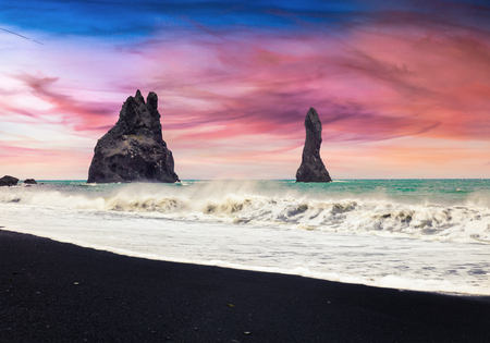Unbelievable seascape of Reynisdrangar cliffs in the Atlantic ocean. Colorful summer sunset in south Iceland, Vic village location, Europe. Artistic style post processed photo.