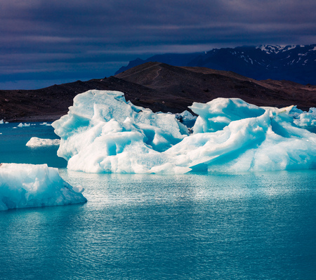 Floating of blue icebergs in Jokulsarlon glacial lagoon. Dramatic evening in Vatnajokull National Park, southeast Iceland, Europe. Artistic style post processed photo. Stock Photo