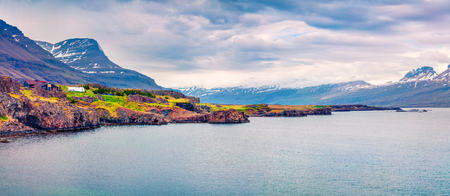 Typical Icelandic landscape with volcanic mountains and Atlantic ocean coast. Sunny summer panorama of the the north coast of Iceland, Europe. Artistic style post processed photo.