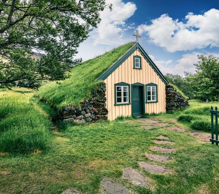 Schilderachtige turf-topkerk in klein dorp Hof. Kleurrijke ochtend in Skaftafell in Nationaal Park Vatnajokull, zuidoostenijsland, Europa. Artistieke stijl na verwerkte foto. Stockfoto